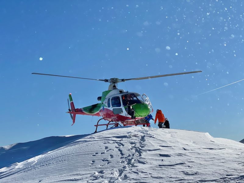 red, green and white helicopter on top of a snow capped mountain against a blue sky