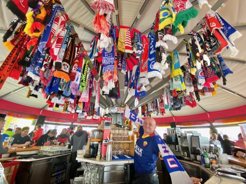 Range of football scarves from different teams with PlanetSKI editor sporting posing with one